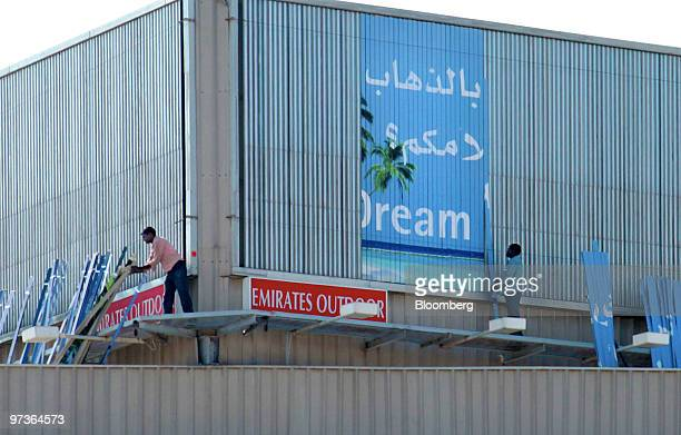 Workers remove a billboard advertisement in Dubai United Arab Emirates on Monday March 1 2010 The United Arab Emirates may take steps to boost bank...