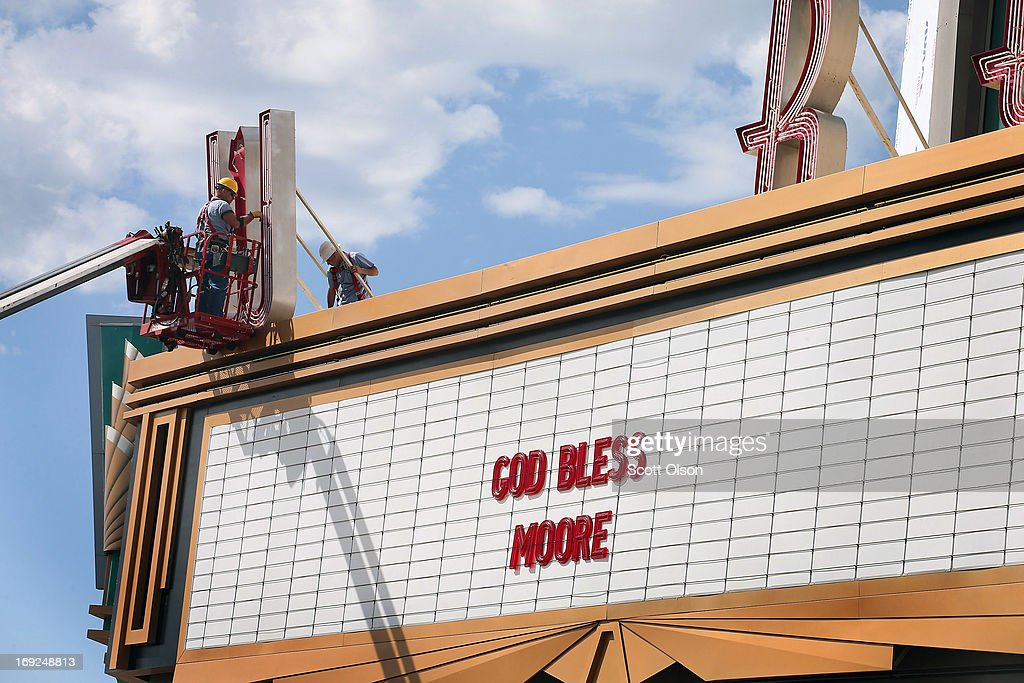 Workers remove a damaged neon letter from the marquee in front of the Warren Theater after a tornado ripped through the area on May 22, 2013 in Moore, Oklahoma. The tornado of at least EF5 strength and two miles wide touched down May 20 killing at least 24 people and leaving behind extensive damage to homes and businesses. U.S. President Barack Obama promised federal aid to supplement state and local recovery efforts.