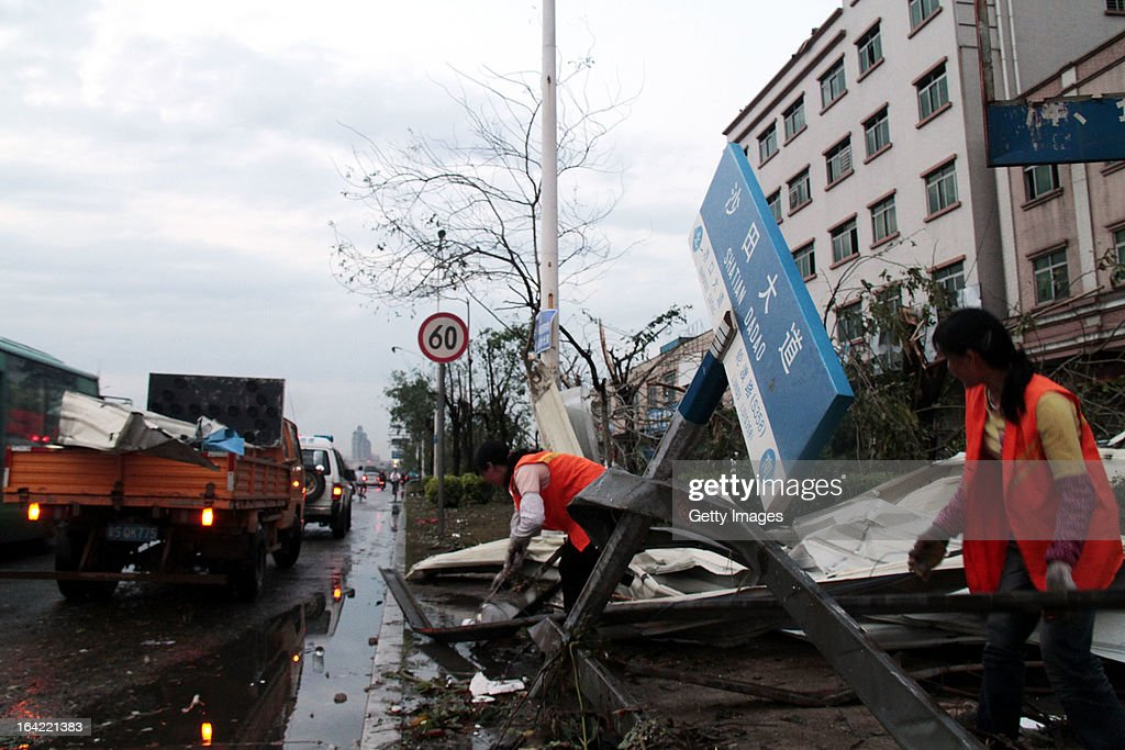 Workers remove a fallen road sign on March 20, 2013 in Dongguan, China. Nine people have been killed and about 272 others injured after a thundersand hailstorm swept Dongguan city on Wednesday afternoon.