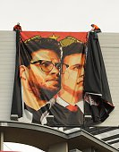 Workers remove a posterbanner for 'The Interview' from a billboard in Hollywood California December 18 2014 a day after Sony announced it had no...