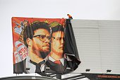 Workers remove a posterbanner for 'The Interview' from a billboard in Hollywood California December 18 2014 a day after Sony announced was cancelling...