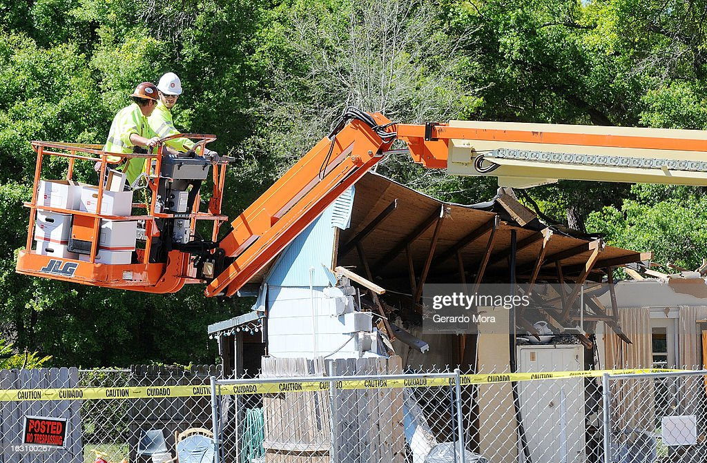 Workers remove belongings from the home where a sinkhole swallowed Jeffrey Bush on March 4, 2013 in Seffner, Florida. Jeff Bush, presumed dead after a sinkhole, estimated at 60 feet deep, opened under his bedroom while he was sleeping in the home. Demolition crews are working to raze the house, recover possessions, and stabilize the now-shaky ground.