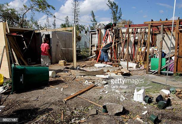 Workers remove debris from Paradise Flowers Plants that has not had the power restored October 28 2005 in Miami Florida Millions remain without power...