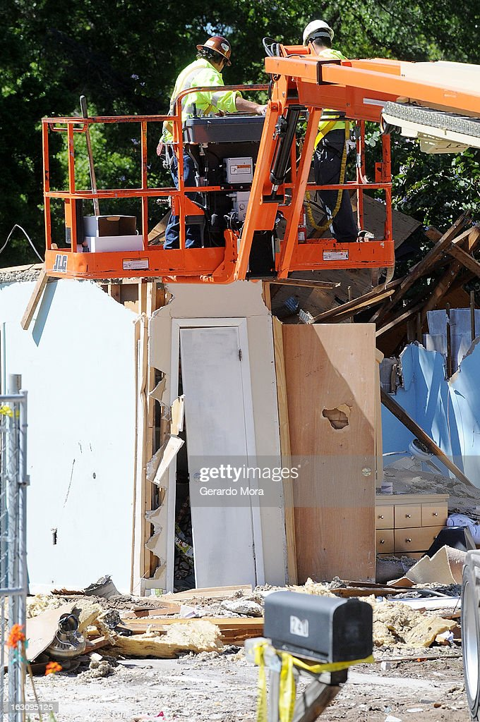 Workers remove debris from the home where a sinkhole swallowed Jeffrey Bush on March 4, 2013 in Seffner, Florida. Jeff Bush, presumed dead after a sinkhole, estimated at 60 feet deep, opened under his bedroom while he was sleeping in the home. Demolition crews are working to raze the house, recover possessions, and stabilize the now-shaky ground.