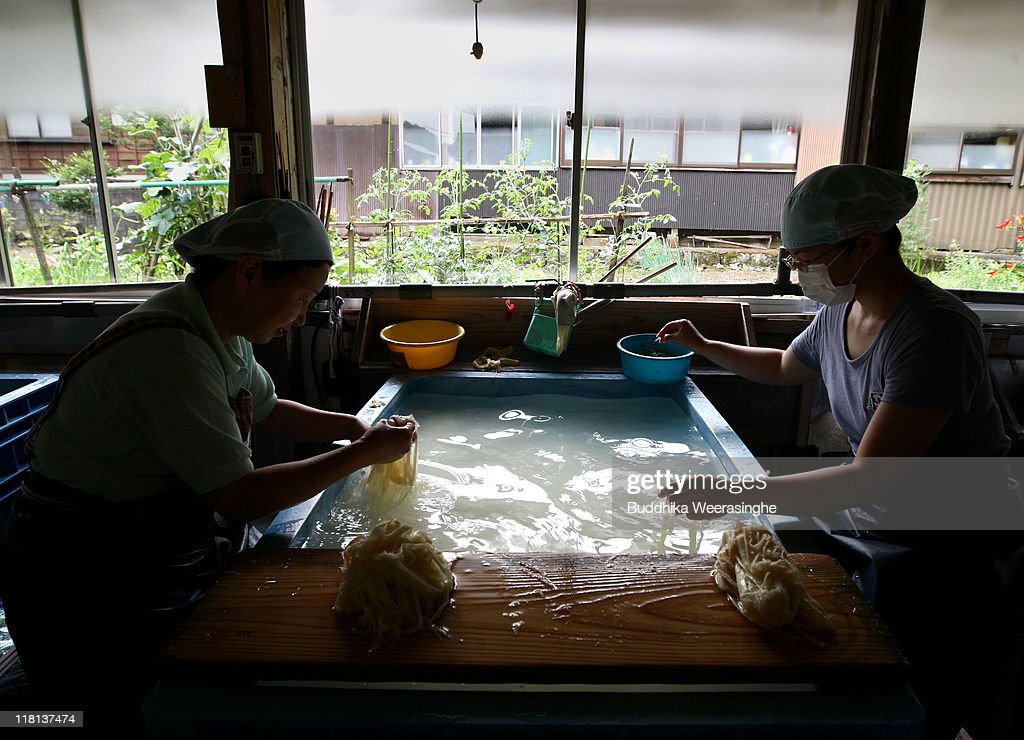 Workers remove dust from a vat of Gampi wood at a mill that produces handmade paper at Iwano Heizaburo Seishi Sho Company in Echizen paper village on July 4, 2011 in Fukui, Japan. Washi paper is a tough paper, used for traditional Japanese arts such as Origami and Shodo, most commonly made from bark of the mulberry, gampi or mitsumata. The paper milling process is a traditional craft of the Echizen people dating back 1500 years which continues today along with modern paper manufacturing. Echizen city is home to many paper businesses, as well as the cultural museum of paper and papyrus centre where visitors can make their own paper. (Photo by Buddhika Weerasinghe/Getty Images)s)