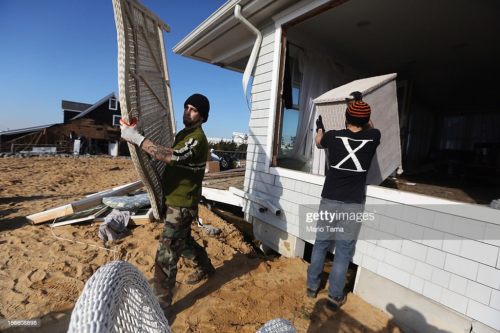 Workers remove items from a damaged home on November 21, 2012 in Mantoloking, New Jersey. Mantoloking was one of the hardest hit areas by Superstorm Sandy.