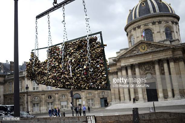 Workers remove love padlocks attached on the railings of the Pont des Arts on June 1 2015 in Paris Started by tourists in Paris in 2008 the love...