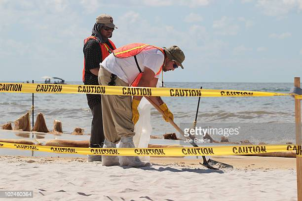Workers remove oil residue as it washes ashore from the Deepwater Horizon oil spill in the Gulf of Mexico on June 27 2010 in Orange Beach Alabama...