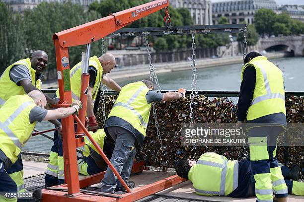 Workers remove panels bearing 'love padlocks' attached on the railings of the Pont des Arts bridge in Paris on June 1 2015 Started by tourists in...