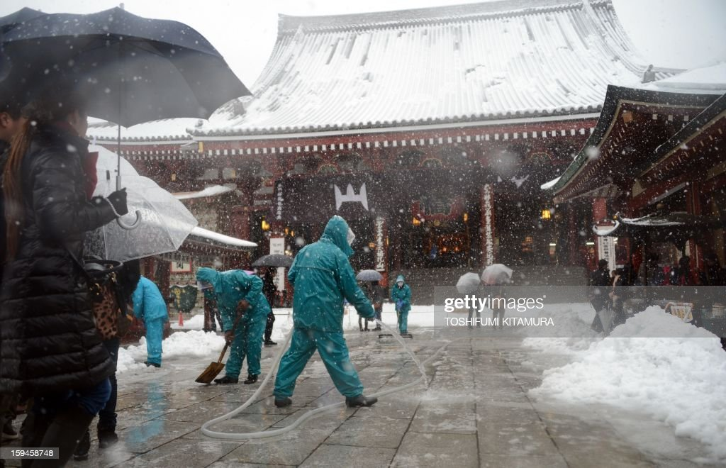Workers remove snow at Sensoji temple in the Asakusa area in Tokyo on January 14, 2013. A storm system grasped central Japan on January 14, causing heavy snow fall around the Japanese capital.