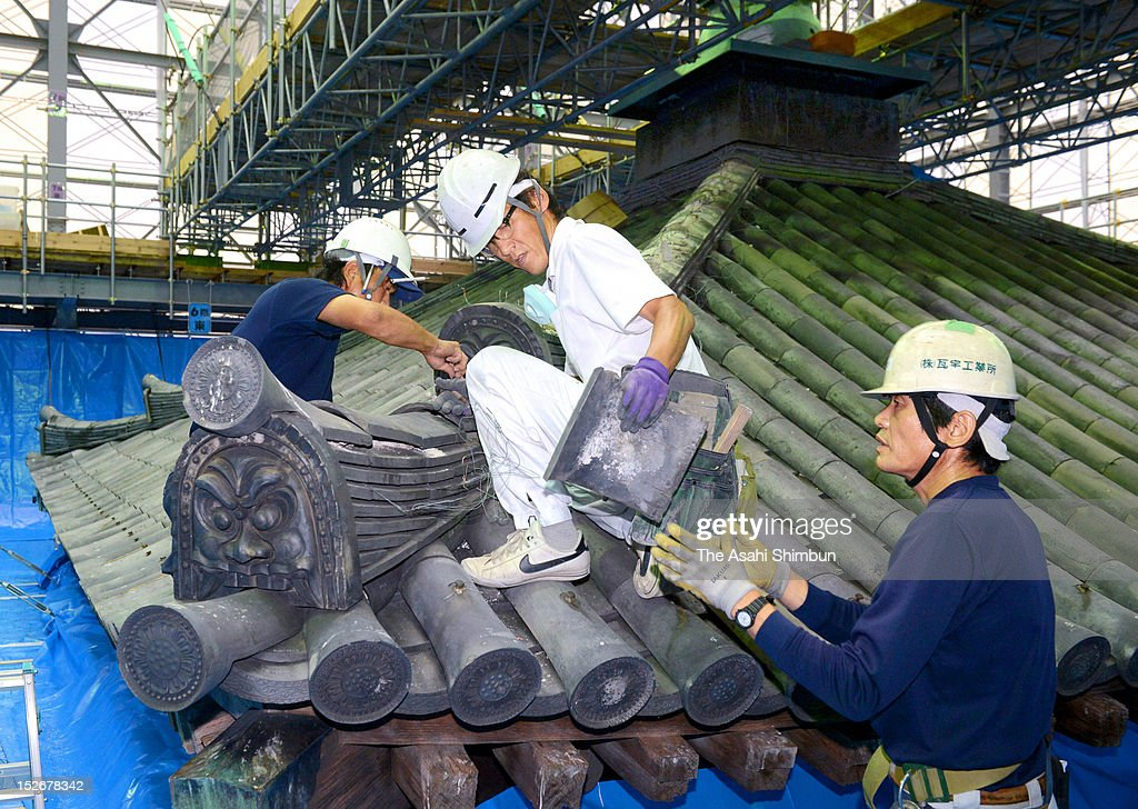 Workers remove the tiles of the Toto, or east tower of Yakushiji Temple on September 14, 2012 in Nara, Japan.
