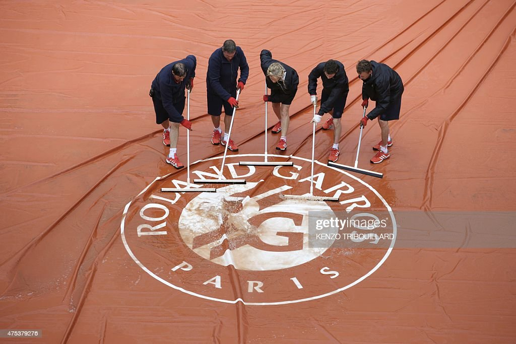 Workers remove water from the protective canvas sheet covering the court as the match opposing Serbia's Ana Ivanovic to Russia's Ekaterina Makarova is interrupted by rain during the women's fourth round at the Roland Garros 2015 French Tennis Open in Paris on May 31, 2015.