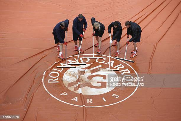 Workers remove water from the protective canvas sheet covering the court as the match opposing Serbia's Ana Ivanovic to Russia's Ekaterina Makarova...