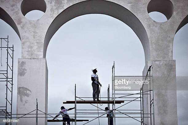 Workers repaint the Arcos de Lapa aqueduct which now serves as a bridge that that connects the city center with the Santa Teresa neighborhood in Rio...