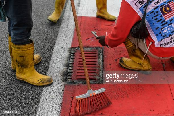 Workers repair a drain cover after Haas F1's French driver Romain Grosjean suffered a frightening tyre explosion during the second practice session...