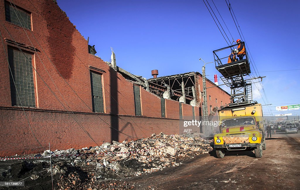 Workers repair a power line near the wall of a local zinc plant which was damaged by a shockwave from a meteor in the Urals city of Chelyabinsk, on February 15, 2013. A meteor strike in central Russia that left today hundreds of people injured is the biggest known human toll from a space rock, a British expert said. AFP PHOTO / 74.RU/ OLEG KARGOPOLOV SOURCE--