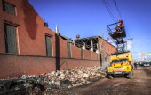 Workers repair a power line near the wall of a local zinc plant which was damaged by a shockwave from a meteor in the Urals city of Chelyabinsk on...