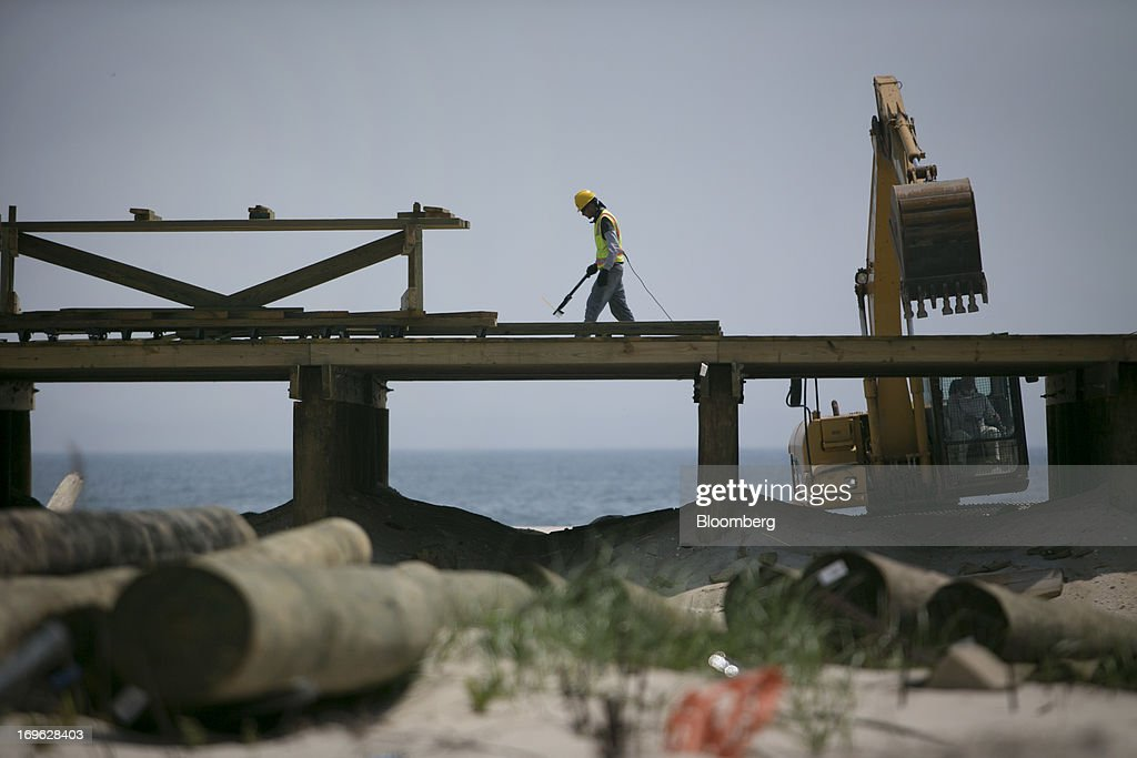 Workers repair a section of the boardwalk in Seaside Heights, New Jersey, U.S., on Wednesday, May 29, 2013. Sandy, which came ashore near Atlantic City, killed dozens of people and destroyed more than 365,000 homes in the state. Christie has said it will cost $36.9 billion for repairs and to prevent devastation from future storms. Photographer: Scott Eells/Bloomberg via Getty Images