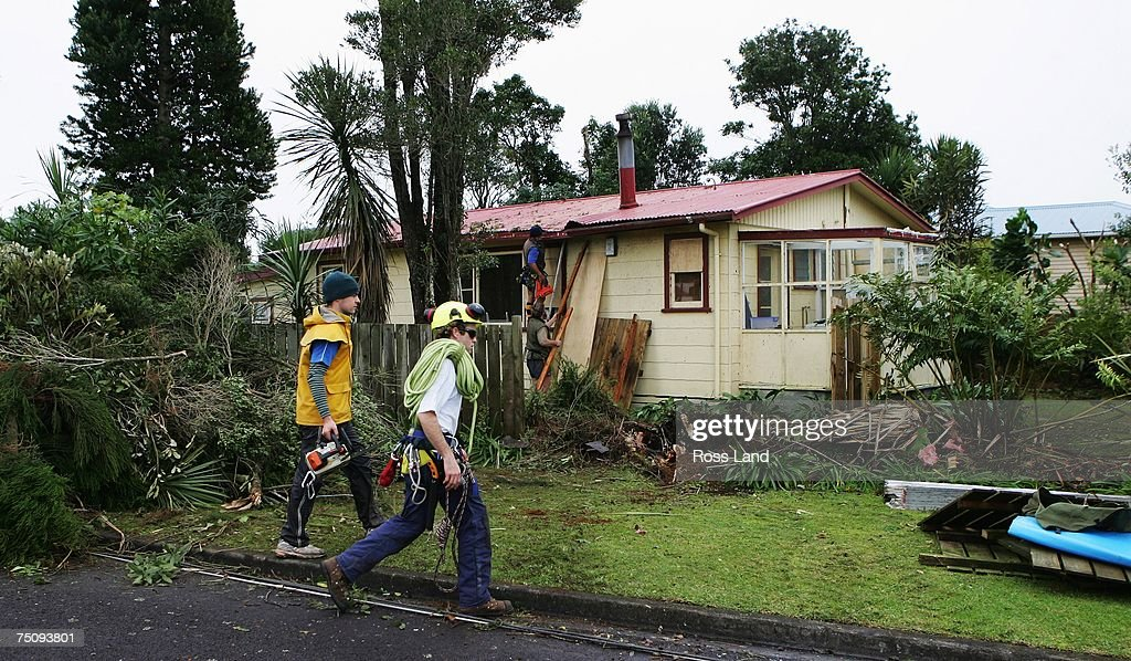 Workers repair damage at a property on July 6 2007 in the town of Oakura south west of New Plymouth New Zealand A state of emergency was declared in...