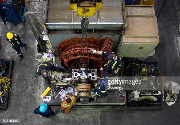 Workers repair one of the five grinders that shave the wood fibers to create pulp for paper at the Resolute Forest Products mill in Thunder Bay...