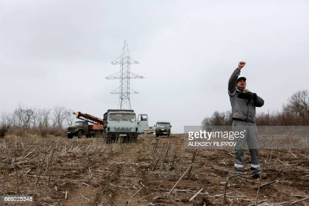 Workers repair power lines damaged by shelling between Ukrainian forces and the Russianbacked rebels near the governmentheld town Avdiivka Donetsk...