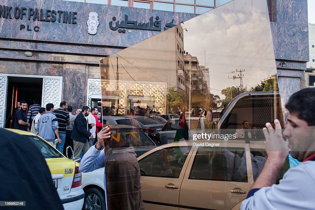 Workers replace the glass in the Bank of Palestine building as lines of people wait to withdraw cash from the ATMs the day after the ceasefire was agreed, in Gaza City Gaza on November 22, 2012.