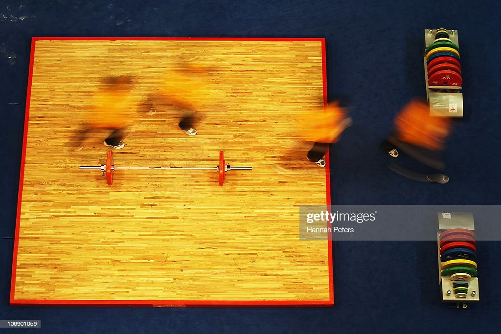 Workers replace waits on the bar ahead of the Men's Weightlifting 77kg competition during day four of the 16th Asian Games Guangzhou 2010 at Dongguan Gymnasium on November 16, 2010 in Guangzhou, China.