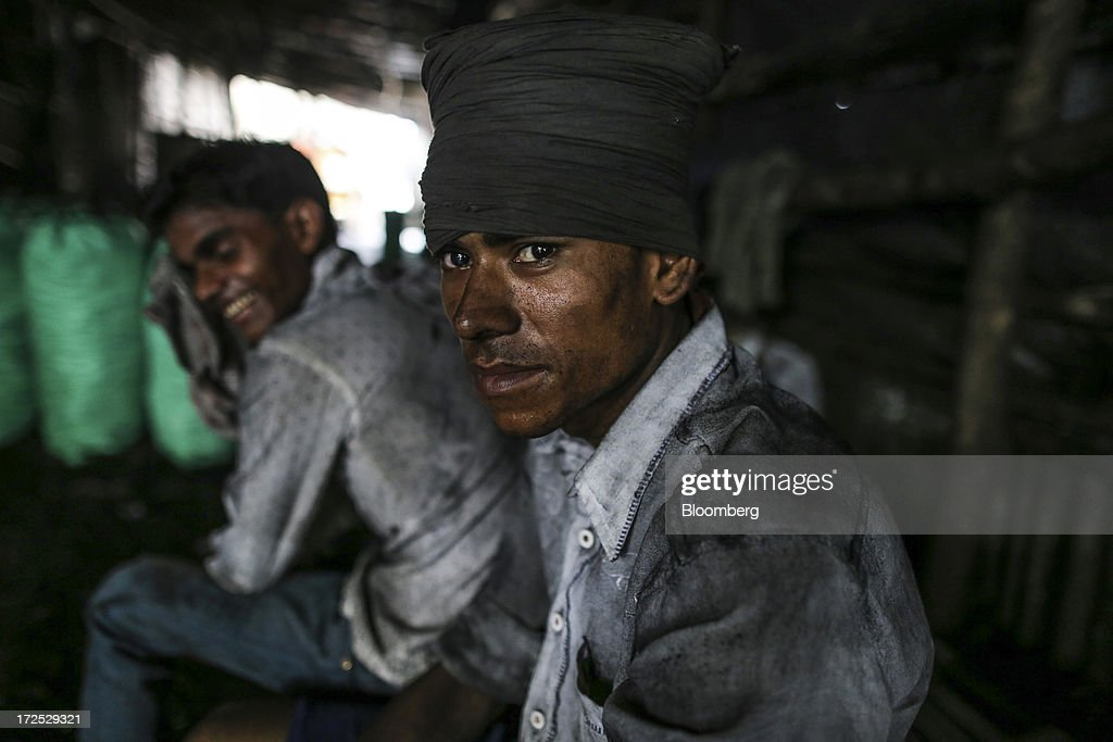 Workers rest during a break at a coal wholesale market in Mumbai, India, on Tuesday, July 2, 2013. India, the worlds third-largest coal consumer, imported 43 percent more of the fuel than a year ago on increased demand from power stations and steelmakers, according to shipping data, and is set to eclipse China as the top importer of power station coal by 2014. Photographer: Dhiraj Singh/Bloomberg via Getty Images