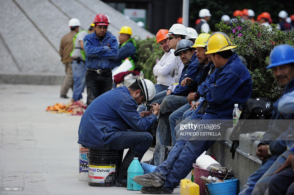 Workers rest outside the damaged building of Mexican state-owned oil giant Pemex, after a blast, in Mexico City on February 5, 2013. A gas build-up caused the explosion that rocked the headquarters of Mexico's state-owned oil firm last week, killing 37 people, officials said Monday, ruling out a bomb attack. The explosion also injured morfe than 120 people. AFP PHOTO/Alredo Estrella