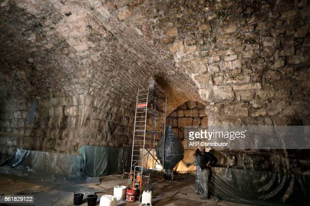Workers restore a ceiling of the Western Wall tunnels near the site where Israeli Antiquity Authority recently discovered an ancient roman theatre...