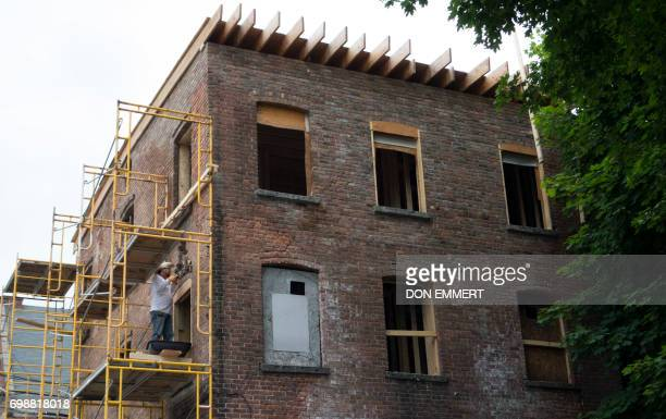 Workers restore a 'zombie' property which was once a delicatessen on May 30 in Newburgh New York Rows of boardedup homes became a ubiquitous symbol...