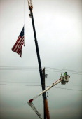 Workers restore power lines after a massive tornado passed through the town killing at least 132 people on May 27 2011 in Joplin Missouri The town...