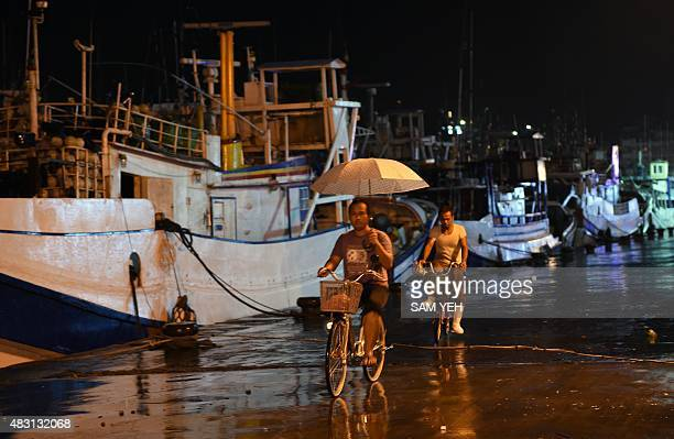 Workers ride past fishing boats moored in a shelter at Nanfangao harbour in Yilan on August 6 2015 as typhoon Soudelor approaches eastern Taiwan The...