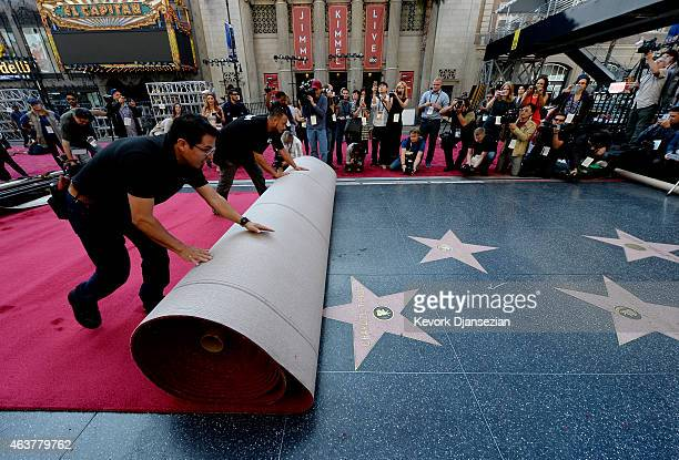 Workers Rodolfo Morales and Ernest Jauregui roll out the ceremonial red carpet over the Hollywood Walk of Fame stars on Hollywood Boulevard in...