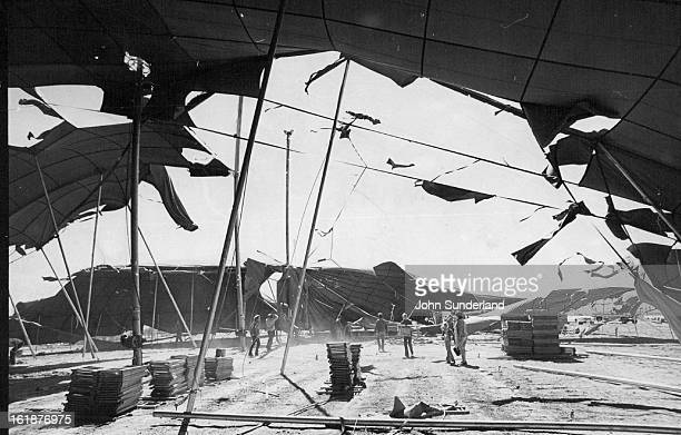 JUN 9 1976 JUN 15 1976 Workers Save what They Can From Winds Workmen remove folding chairs and other equipment from a large revival tent as strong...