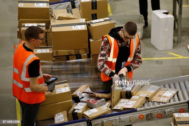 Workers scan orders for shipment at an Amazoncom Inc fulfillment center in Peterborough UK on Wednesday Nov 15 2017 As Amazon's share of retail sales...