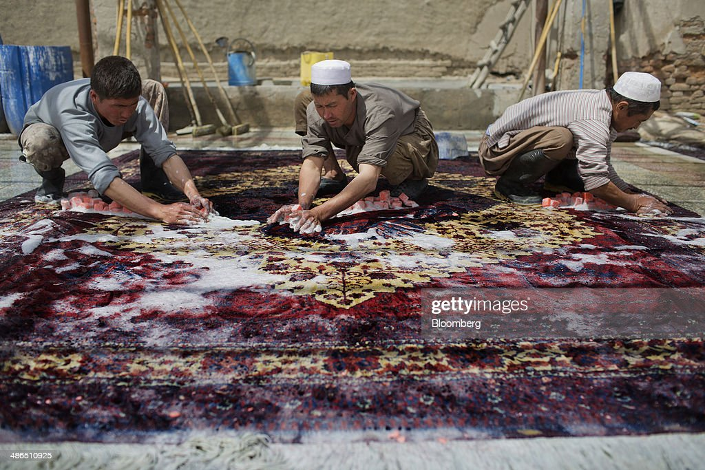 Workers scrub a finished rug at a facility to clean and trim handmade carpets in Kabul, Afghanistan, on Monday, April 14, 2014. Afghanistan's economic growth in 2013 was 3.6 percent, down sharply from 14.4 percent in 2012, primarily due to heightened uncertainty surrounding the political and security transition, according to a World Bank report. Photographer: Victor J. Blue/Bloomberg via Getty Images