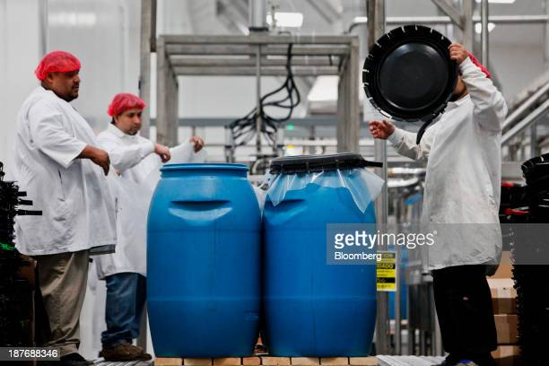 Workers seal large drums of ground up chili pepper mash stacked for storage before being mixed and bottled into Sriracha hot sauce at the Huy Fong...