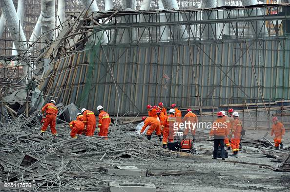 Workers search for survivors in the debris of a collapsed platform in a cooling tower at a power station at Fengcheng in China's Jiangxi province on...