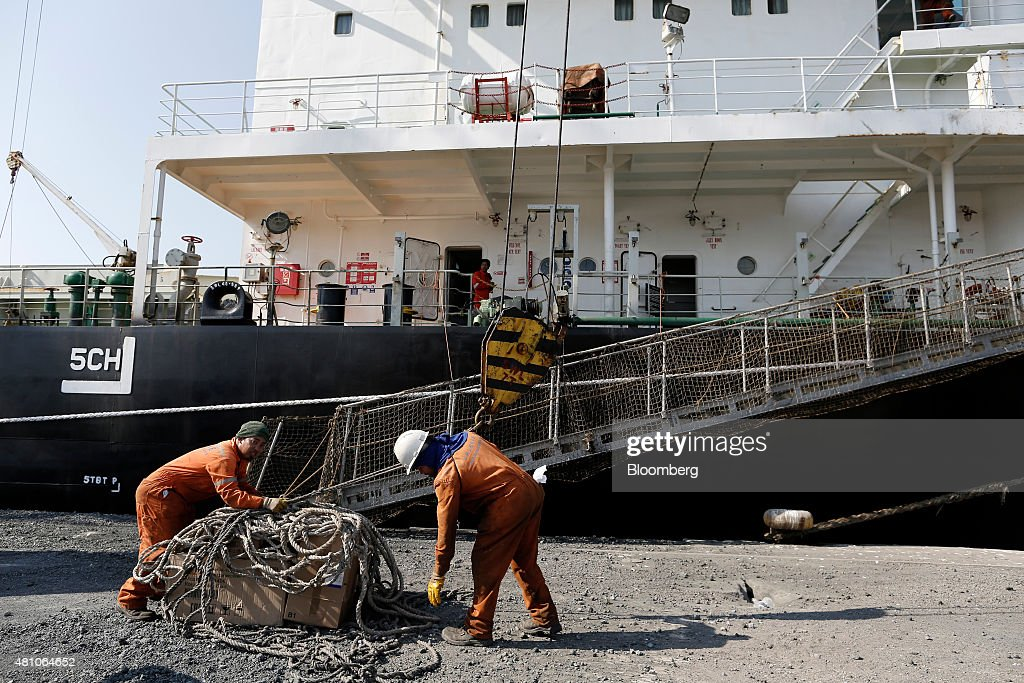 Workers secure a winch as they load goods onto a cargo ship on the dockside at Thessaloniki port operated by Thessaloniki Port Authority SA in...