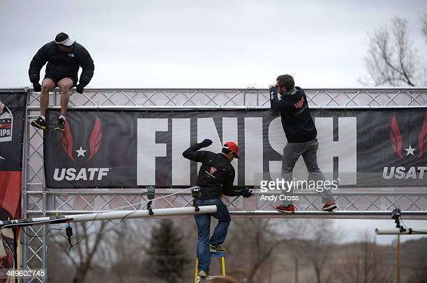 Workers secure the finish line banner at the USA Cross Country Championships at the Flatirons Golf Course Saturday afternoon February 15 2013