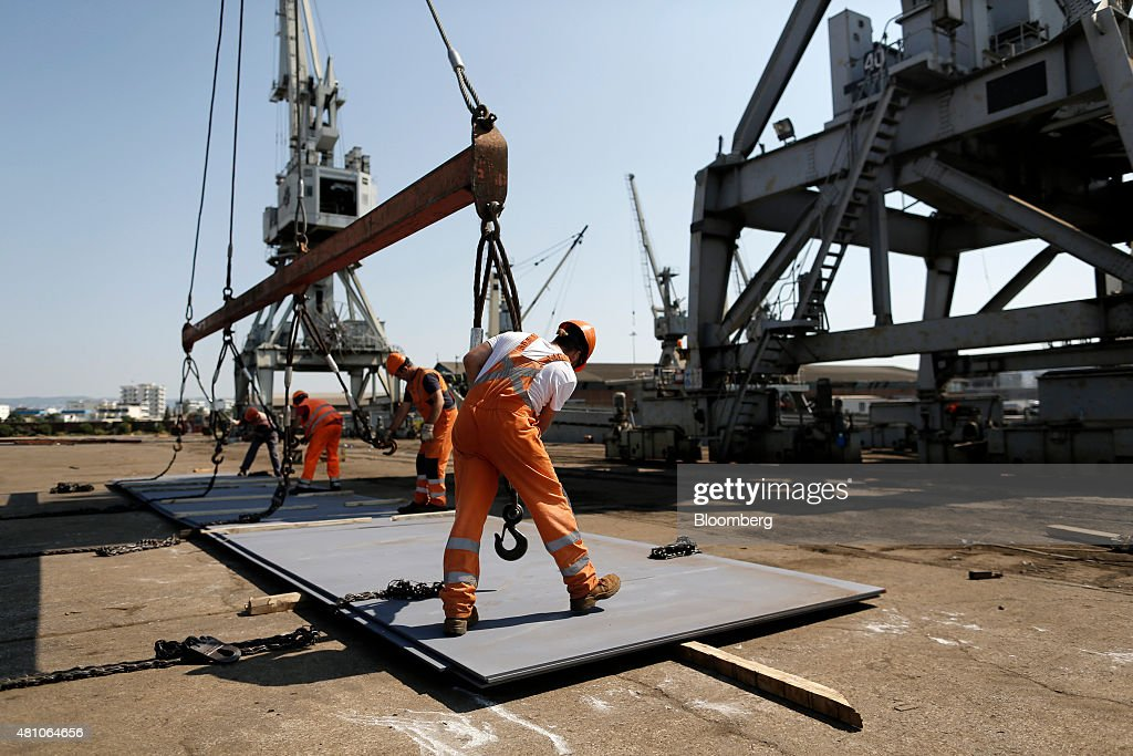 Workers secure winches as they load sheets of metal onto a cargo ship on the dockside at Thessaloniki port operated by Thessaloniki Port Authority SA...