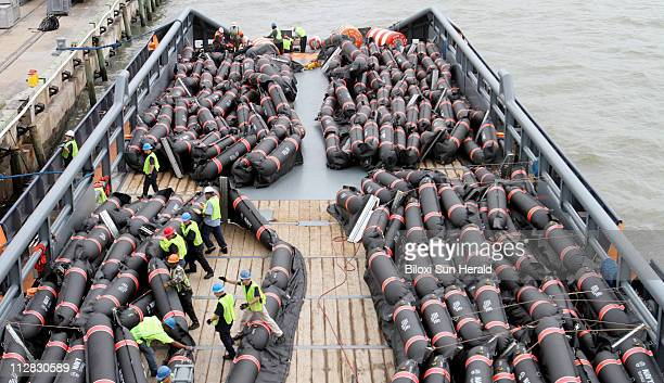 Workers secures inflatable oil containment booms on the deck of an offshore service vessel at the Mississippi State Port in Gulfport Mississippi...