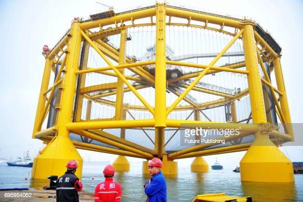 Workers see off the smart deepsea salmon farm leaving the shipyard in east China's Shandong province for a journey to Norway on June 14 2017 in...