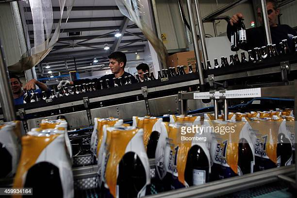 Workers select bottles of FIX Hellas beer as they move along the production line during the packaging process at Olympic Brewery SA's beer production...