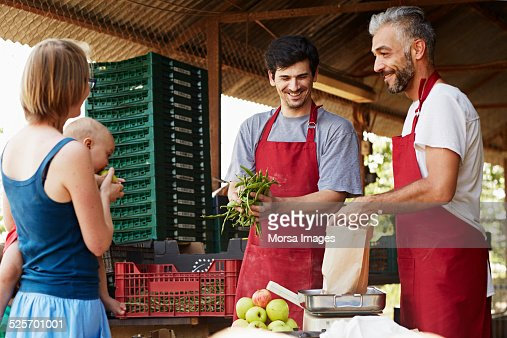 workers selling produce to woman at organic farm