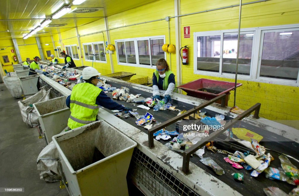 Workers separate different types of waste for recycling at a waste treatment plant in Palma de Mallorca on January 17, 2013. AFP PHOTO / Jaime REINA