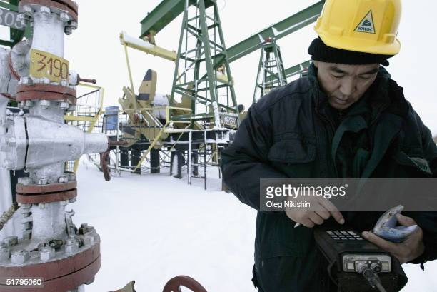 YUKOS workers servicing an oil well November 11 2004 on the UstBalick oil field near Nefteyugansk West Siberia Russia Russia's natural gas monopoly...
