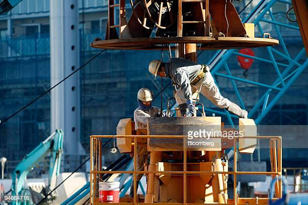Workers set a boring machine on a construction site in Tokyo Japan on Thursday Nov 22 2007 Japan's thirdquarter expansion was lower than the...