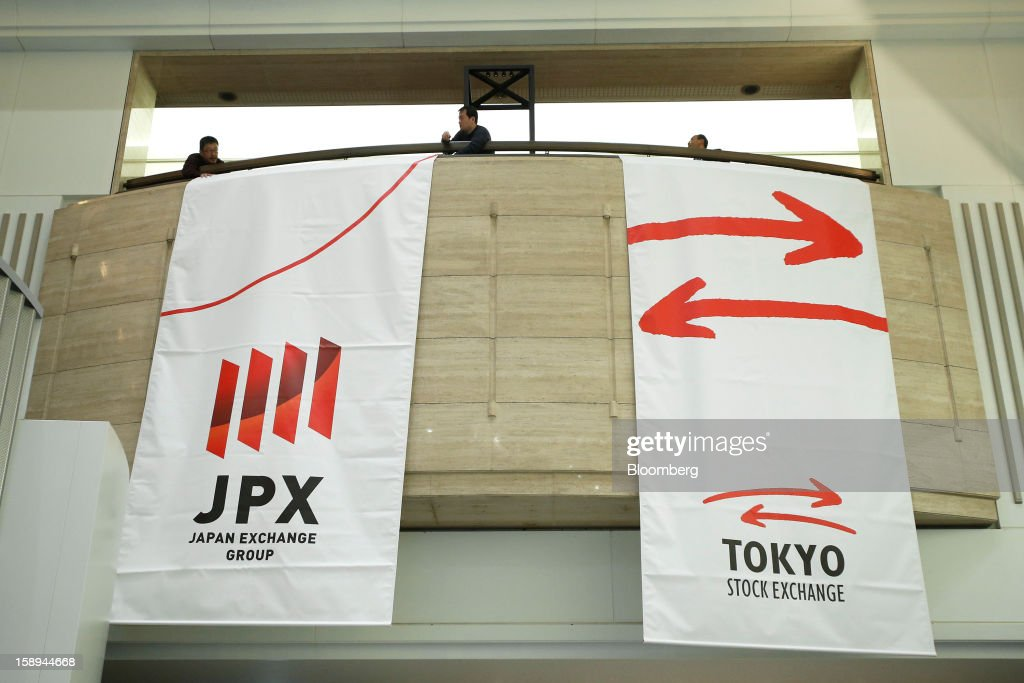 Workers set a flag bearing the logo of Japan Exchange Group, Inc., left, on a wall at the Tokyo Stock Exchange (TSE) on the first trading day of the year in Tokyo, Japan, on Friday, Jan. 4, 2013. Japan Exchange, created by the merger of Japan's two biggest bourses, fell in its trading debut on the Tokyo Stock Exchange. Photographer: Kiyoshi Ota/Bloomberg via Getty Images